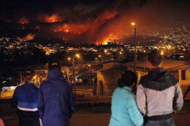 In this April 13, 2014 file photo, people watch as a forest fire rages towards urban areas in the city of Valparaiso, Chile. Authorities say the first fire has destroyed at least 150 homes and is forcing evacuations. (Photo by Luis Hidalgo/AP Photo)