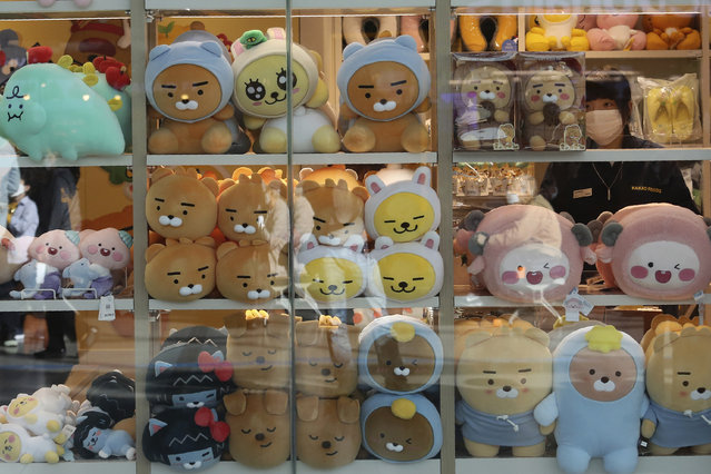An employee wearing a face mask to help protect against the spread of the coronavirus arranges dolls at a shop in Seoul, South Korea, Thursday, October 22, 2020. The steady spread of the coronavirus caused concern in a country that eased its social distancing restrictions just last week to cope with a weak economy. (Photo by Ahn Young-joon/AP Photo)
