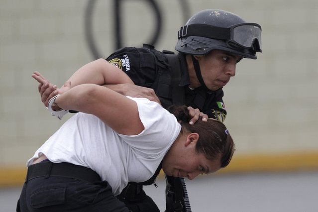 A member of the Fuerza Civil (Civil Force) police unit takes part in a simulated crime situation during a media presentation to show the police model that the federal government wants for the rest of the country, at the police academy in Monterrey December 17, 2014. (Photo by Daniel Becerril/Reuters)