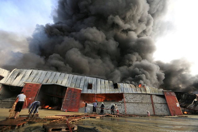 Firefighters try to extinguish a fire engulfing warehouse of the World Food Programme in Hodeida, Yemen March 31, 2018. (Photo by Abduljabbar Zeyad/Reuters)