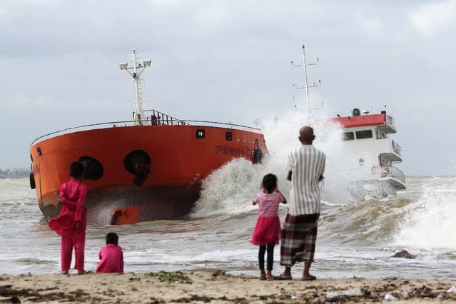 Locals watch from the beach as waves hit an Indonesian tanker that ran aground near Narathiwat in southern Thailand December 19, 2014. The tanker loaded with palm oil, previously hijacked by its crew members and then seized by Thai authorities, was anchored some 400 meters from the beach but strong wind and waves broke it free, according to local media. (Photo by Surapan Boonthanom/Reuters)