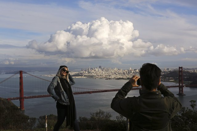 Visitors to the Marin Headlands pose for photographs overlooking the Golden Gate Bridge and skyline of San Francisco, as a large cloud gathers over the city, December 12, 2014. A major storm pummeled California and the Pacific Northwest with heavy rain and high winds on Thursday, killing one man, knocking out power to tens of thousands of homes, disrupting flights and prompting schools to close. (Photo by Robert Galbraith/Reuters)