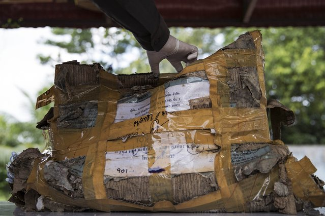 A policeman opens a box with personal possessions of 2004 tsunami victims to be photographed outside a police station in Takua Pa, in Phang Nga province December 19, 2014. (Photo by Damir Sagolj/Reuters)