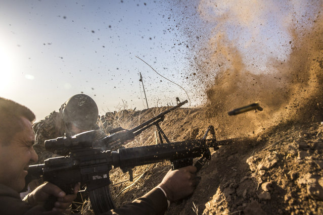 Kurdish pesh merga troops fire at Islamic State positions as they move toward the Iraqi town of Badana Pichwk on Monday morning, October 17, 2016. Kurdish forces began Monday advancing on a string of villages east of Mosul, the start of a long-awaited campaign to reclaim Iraq's second-largest city from the Islamic State, which seized it more than two years ago, officials said. (Photo by Bryan Denton/The New York Times)