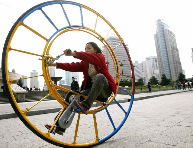 "A woman rides an unicycle at a park in Shanghai February 28, 2004. The unicycle was designed by Chinese inventor Li Yongli who called it ""the number one vehicle in the world"". (Photo by Reuters/China Photos)"