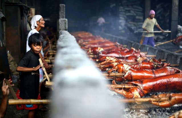 A 10-year-old Filipino boy turns a bamboo pole as he helps his parents work at a pig roasting pit in suburban Quezon city, Philippines on Tuesday, December 23, 2014. (Photo by Aaron Favila/AP Photo)