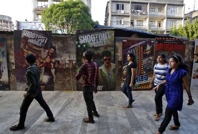 People walk past Bollywood film posters in Mumbai April 14, 2013. (Photo by Danish Siddiqui/Reuters)