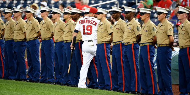 Field of Marines. Washington Nationals Kevin Frandsen (19) slips though a line of Marines prior to the playing of the national anthem prior to game action against the Arizona Diamondbacks on August 20,  2014 in Washington, DC. (Photo by Jonathan Newton/The Washington Post)