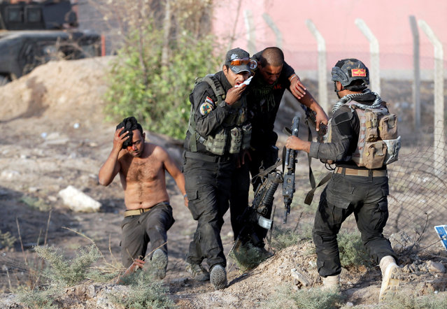 Wounded Iraqi special forces soldiers react during clashes with Islamic Sates fighters in Bartella, east of Mosul, Iraq October 20, 2016. (Photo by Goran Tomasevic/Reuters)