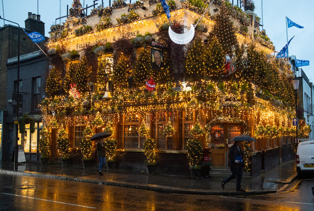 People pass Christmas lights outside the closed Churchill Arms pub in Kensington, west London on December 16, 2020, after the capital moved into the highest tier of coronavirus restrictions as a result of soaring case rates. (Photo by Dominic Lipinski/PA Images via Getty Images)