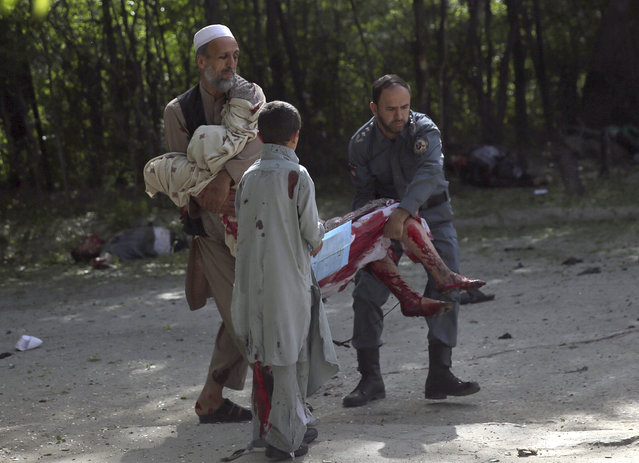 A wounded woman is helped at the site of explosions, in Kabul, Afghanistan, Monday, April 30, 2018. The explosions targeted central Kabul on Monday morning, killing people and wounding a dozen, authorities said, (Photo by Massoud Hossaini/AP Photo)