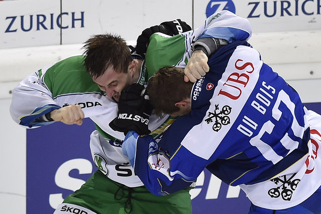 Ufa's Anton Slepyshev, left, fights against Davo's Felicien du Bois during the game between Switzerland's HC Davos and Russia's HC Salavat Yulaev Ufa in the semi final game at the 88th Spengler Cup ice hockey tournament in Davos, Switzerland, Tuesday, December 30, 2014. (Photo by Peter Schneider/EPA)