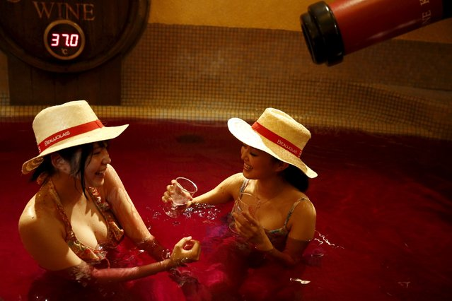 Women drink wine as they sit in a hot bath with coloured water representing wine at the Hakone Kowaki-en Yunessun spa resort during an event marking Beaujolais Nouveau Day in Hakone west of Tokyo, November 19, 2015. (Photo by Thomas Peter/Reuters)