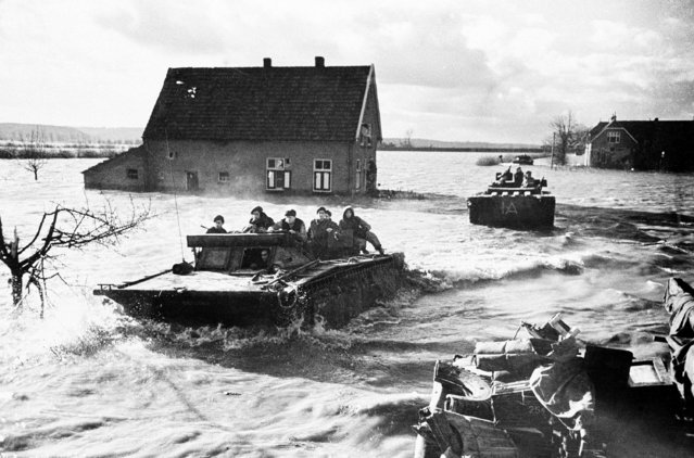 Loaded with Canadian Soldiers, Amphibious Vehicles of the Canadian first Army move across the inundated countryside of a village east of Nijmegen, February 21, 1945 in Netherland, after rescuing soldiers marooned by floods caused when Germans Dynaminated Dyke. (Photo by AP Photo)