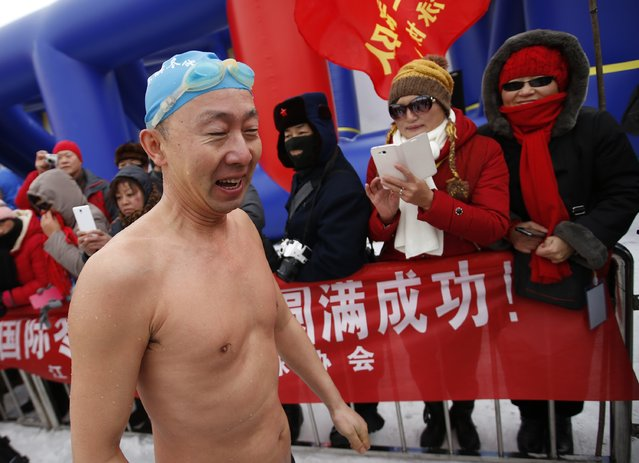 Visitors look at a swimmer who finished his competition in a pool carved into thick ice covering the Songhua River during the Harbin Ice Swimming Competition in the northern city of Harbin, Heilongjiang province January 5, 2015. (Photo by Kim Kyung-Hoon/Reuters)