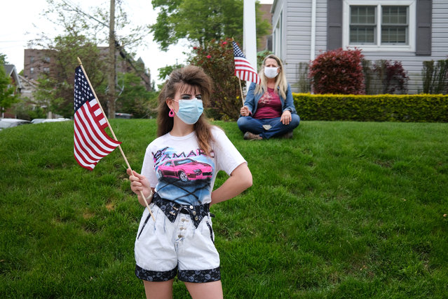 People wear face masks while participating in the annual Memorial Day Parade on May 25, 2020 in the Staten Island borough of New York City. Dozens of cars and nearly 100 members of the patriotic motorcycle group Rolling Thunder joined the event. This year's parade was diminished in size and in person-to-person contact due to the coronavirus outbreak. Across the country, events honoring the nation's veterans have been cancelled or scaled back as America continues to experience high numbers of deaths and new cases of COVID-19. (Photo by Spencer Platt/Getty Images)