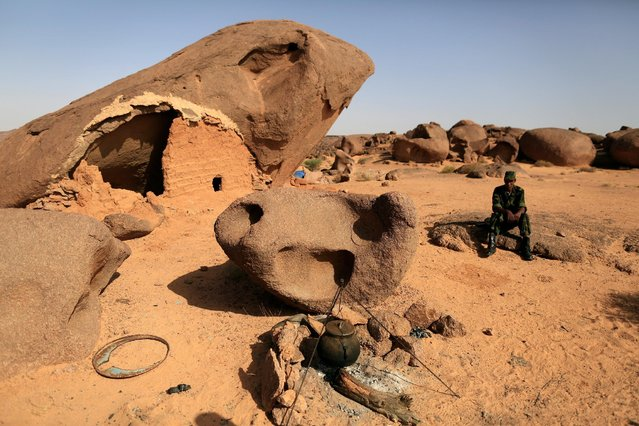 A Polisario fighter sits on a rock at a forward base on the outskirts of Tifariti, Western Sahara, September 9, 2016. At a rocky outpost in Western Sahara, a new generation of soldiers who have never known war are mobilising as tensions resurface in one of Africa's oldest disputes after a quarter century of uneasy peace. Young Sahrawi troops man new desert posts for the Polisario Front, which for more than 40 years has sought independence for the vast desert region - first in a guerrilla war against Morocco and then politically since a ceasefire deal in 1991. Now a standoff with Morocco, which controls the majority of Western Sahara, is renewing pressure for a diplomatic solution to ensure foot soldiers don't return to fighting as the last generation of commanders once did. The standoff since August has brought Moroccan and Polisario forces within 200 metres of each other in a narrow strip of land near the Mauritanian border. Rich in phosphate, Western Sahara has been contested since 1975 when Spanish colonial powers left. Morocco claimed the territory and fought the 16-year war with Polisario. (Photo by Zohra Bensemra/Reuters)