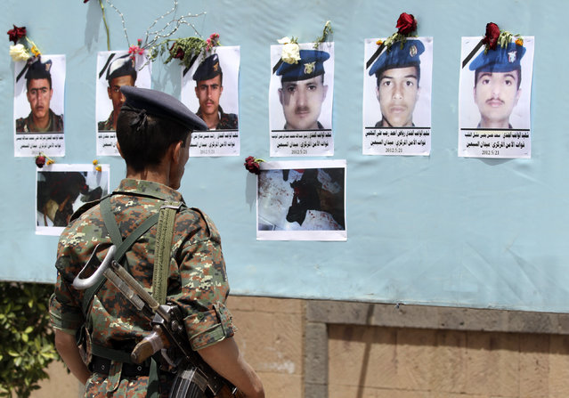 A soldier looks at portraits of victims of a suicide attack, during a protest to condemn the attack that killed more than 90 soldiers, in Sanaa May 29, 2012. (Photo by Mohamed al-Sayaghi/Reuters)