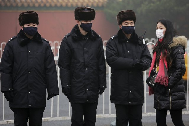 A woman wearing a protective mask talks to policemen, also wearing masks, near the Forbidden City on an extremely polluted day as hazardous, choking smog continues to blanket Beijing, China December 1, 2015. (Photo by Damir Sagolj/Reuters)