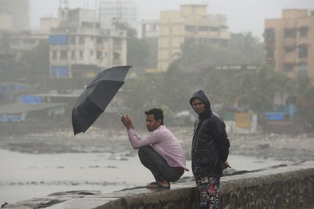 Indians look on by the sea front during heavy rain showers in Mumbai on June 18, 2013. The monsoon, which India's farming sector depends on, covers the subcontinent from June to September, usually bringing some flooding. But the heavy rains arrived early this year, catching many by surprise. The country has received 68 percent more rain than normal for this time of year, data from the India Meteorological Department shows. (Photo by Punit Paranjpe/AFP Photo)