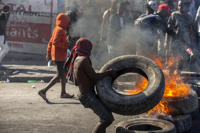 A protester sets up a burning barricade during a protest to demand the resignation of Haitian President Jovenel Moise in Port-au-Prince, Haiti, Sunday, February 7, 2021. (Photo by Dieu Nalio Chery/AP Photo)