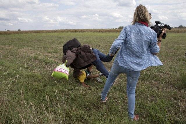 From house breaking in Johannesburg to hippos on the loose in Tbilisi to rioters attacking a policewoman in Burundi, Reuters photographers tell the story behind some of the most iconic pictures of the year. Here: A migrant carrying a child falls after being tripped over by TV camerawoman (R) Petra Laszlo while trying to escape from a collection point in Roszke village, Hungary, September 8, 2015. (Photo by Marko Djurica/Reuters)