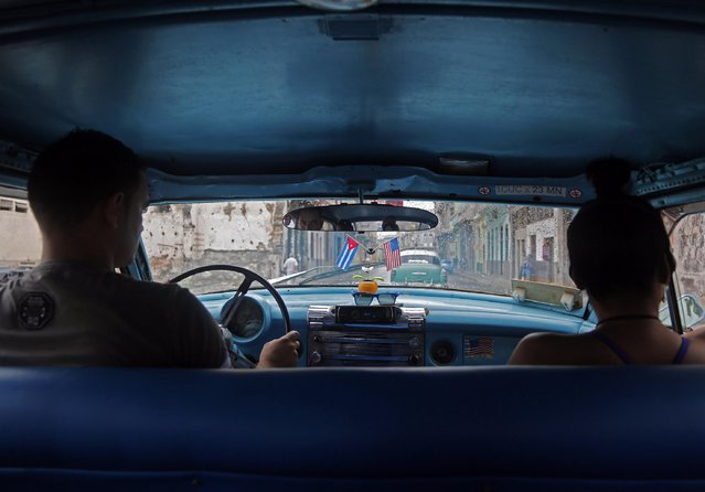 A driver steers his classic American car, used as a collective taxi, along a street in Havana, Cuba, Friday, January 16, 2015. Tens of thousands more American tourists are expected to flock this year to the country where some five-star hotels don't have working air-conditioning or hand towels. (Photo by Desmond Boylan/AP Photo)