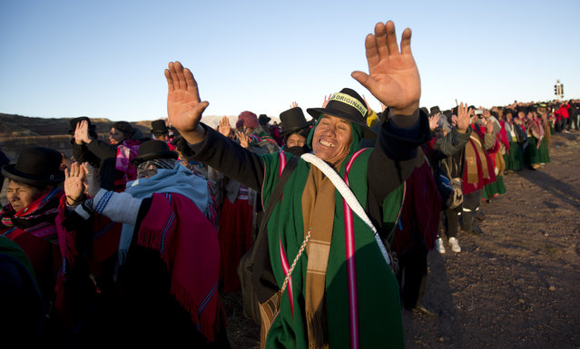 Aymara Indians hold up their hands to receive the first rays of sunlight in a New Year's ritual at the ruins of the ancient city of Tiwanaku, Bolivia, early Thursday, June 21, 2018. Bolivia's Aymara indigenous communities are celebrating the Andean new year 5,526 as well as the Southern Hemisphere's winter solstice, which marks the start of a new agricultural cycle. (Photo by Juan Karita/AP Photo)