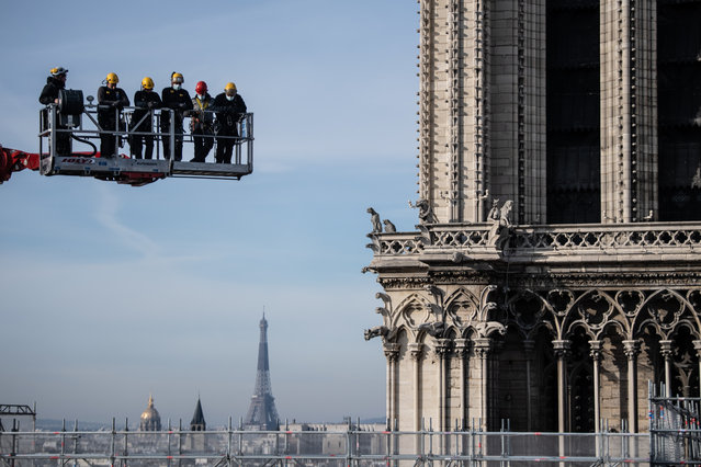 Workers on a crane look at Notre-Dame cathedral site on November 24, 2020 in Paris. The dismantling of the old scaffolding that surrounded the spire of Notre-Dame de Paris before the fire of 15 April 2019 and which hampered the safety of the damaged building, was completed on November 24, 2020. (Photo by Martin Bureau/AFP Photo)