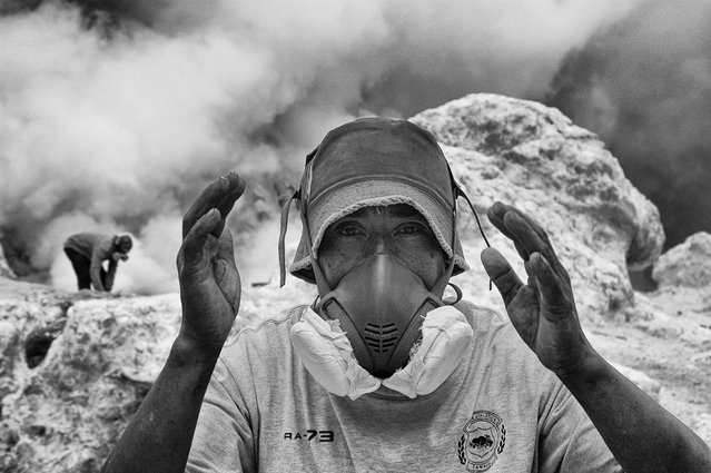 """Working in the hell"". This shot was done in a moment of break of this young guy who works every day as a miner of sulfur in the crater of the volcano Kawa Ijen, southeast of the of Java island, Indonesia. Is one of the most wasting jobs imaginable, work in extreme conditions with high temperatures, toxic exhalations that burning eyes and lungs. The stated life expectancy is 50 years and this guy is more fortunate than other boys like him because he can afford the luxury of working with a mask to filter toxic substances. (Photo and caption by Dario Ruta/National Geographic Traveler Photo Contest)"