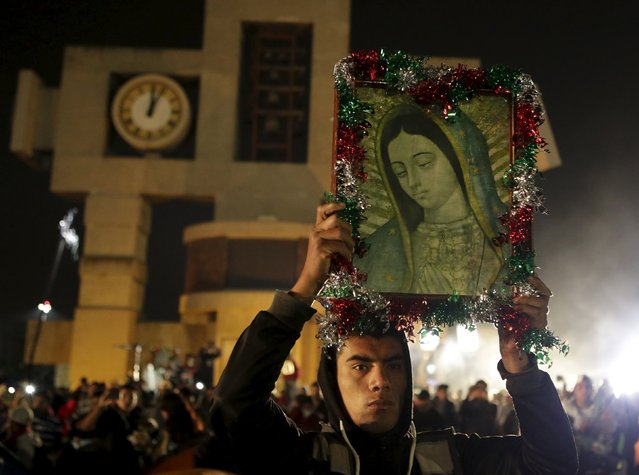 A pilgrim holds up an image of the Virgin of Guadalupe inside the Basilica of Guadalupe during the annual pilgrimage in honor of the Virgin of Guadalupe, patron saint of Mexican Catholics, in Mexico City, Mexico December 12, 2015. (Photo by Henry Romero/Reuters)