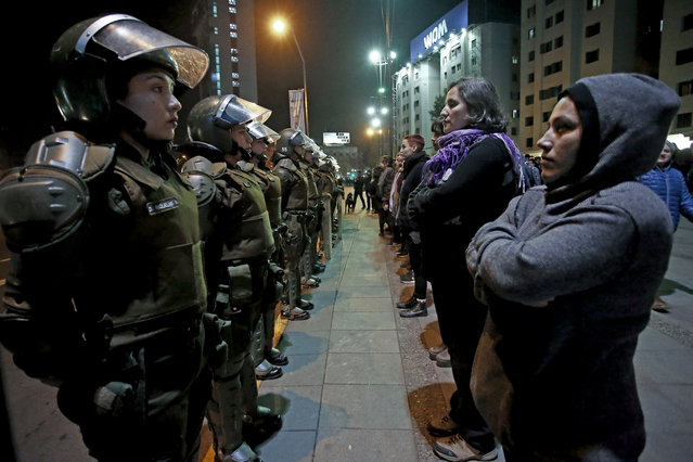 In this June 1, 2018 photo published on June 28, a group of women face a line of policewomen in anti-riot gear, before a march protesting sexual harassment in Santiago, Chile. A seemingly light sanction for a prominent lawyer accused of sexual harassment has ignited protests and takeovers in universities across Chile. (Photo by Luis Hidalgo/AP Photo)