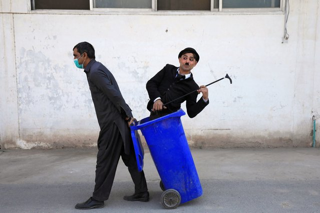 A man pulls a bin with Usman Khan, 29, dressed up as Charlie Chaplin during a street performance in Peshawar, Pakistan on January 28, 2021. (Photo by Fayaz Aziz/Reuters)