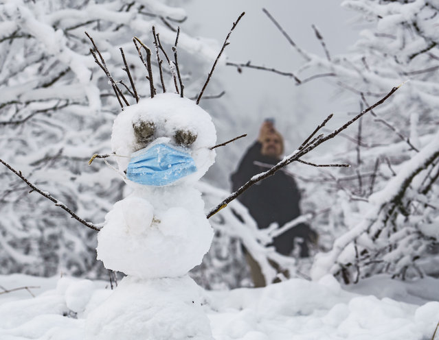A snowman with mouth and nose protection stands on the snow-covered summit plateau of the Grosser Feldberg in the Taunus Mountains, Germany, Monday, December 7, 2020. (Photo by Frank Rumpenhorst/dpa via AP Photo)