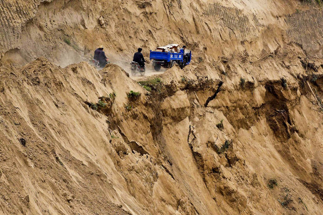 Motorcycles travel on a road near a cliff of a landslide site after a 6.6 magnitude earthquake hit Minxian county, Gansu province, on July 24, 2013. The death toll from two earthquakes in China's western Gansu province has climbed to 95, with more than 500 people severely injured. (Photo by Rooney Chen/Reuters)