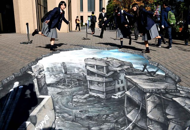 Students pose for a picture with a 3- D optical illusion artwork of a devastated cityscape in Aleppo, Syria at the campus of the Meiji University in Tokyo on November 18, 2016. The Japanese branch of the human rights organisation Amnesty International displayed the artwork to encourage people to think about the Syrian civil war. (Photo by Toshifumi Kitamura/AFP Photo)
