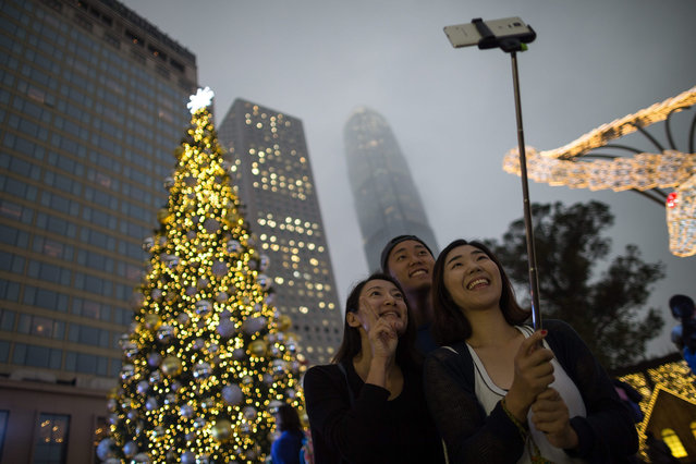 A group of friends take a selfie near a Christmas tree in the business district of Central in Hong Kong, China, 23 December 2015. Christmas is celebrated by Christians on 25 December to commemorate the birth of Jesus, the central figure of Christianity. (Photo by Jerome Favre/EPA)