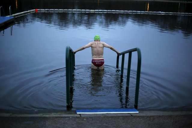 A swimmer takes a dip in the Serpentine River before the annual Christmas Day Peter Pan Cup handicap race in Hyde Park, London, December 25, 2015. (Photo by Andrew Winning/Reuters)