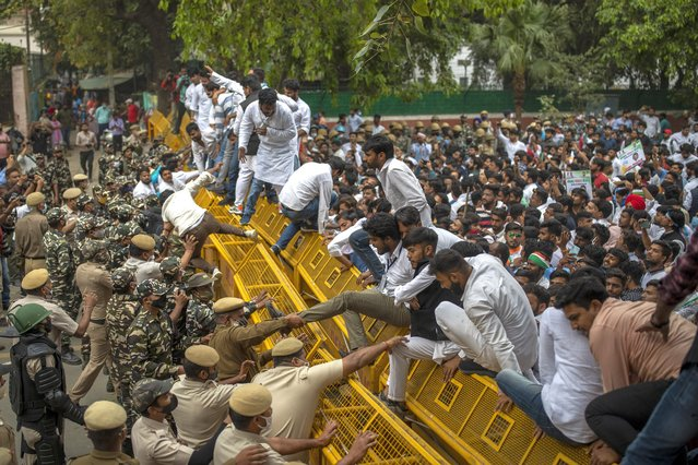 Indian police officers try to pull down members of National Students Union of India (NSUI), the student body of the Congress party, who climbed on police barricades during a protest against rising unemployment in the country in New Delhi, India, Friday, March 12, 2021. (Photo by Altaf Qadri/AP Photo)