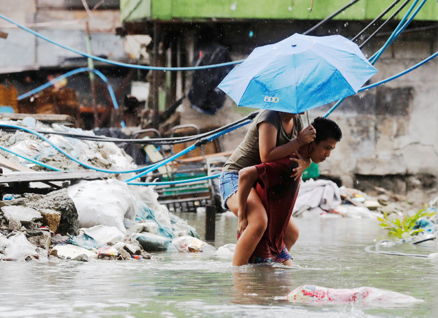 A resident carries a woman on his back along a flooded street caused by monsoon rains and Tropical Storm Son-Tinh in Quezon city, Metro Manila, Philippines on July 17, 2018. (Photo by Erik De Castro/Reuters)