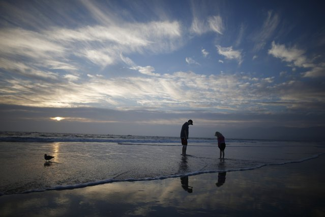 A man and a girl paddle in the Pacific Ocean at sunset in Santa Monica, California February 5, 2015. (Photo by Lucy Nicholson/Reuters)