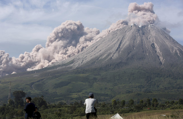 People watch as Mount Sinabung spews volcanic materials during an eruption in Karo, North Sumatra, Indonesia, Thursday, March 11, 2021. The volcano unleashed an avalanche of searing gas clouds flowing down its slopes during eruption on Thursday. No casualties were reported. (Photo by Binsar Bakkara/AP Photo)