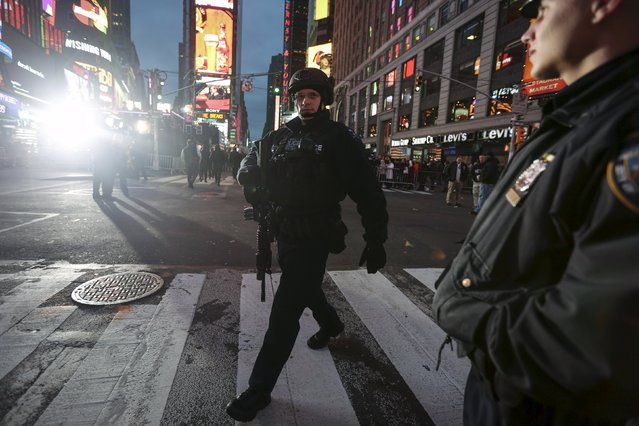 An Emergency Services Unit officer with a long gun walks on patrol through Times Square during New Year's Eve celebrations in the Manhattan borough of New York December 31, 2015. (Photo by Carlo Allegri/Reuters)
