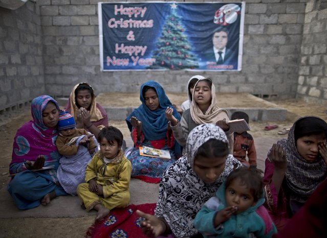 In this Friday, February 6, 2015 photo, Pakistani Christians pray before starting class at a makeshift church in a slum home to Christian families on the outskirts of Islamabad, Pakistan. (Photo by Muhammed Muheisen/AP Photo)