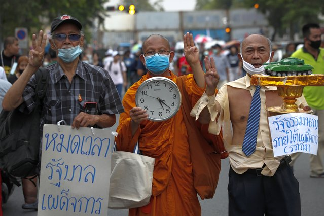 A Thai Buddhist monk (C) joins a rally calling to revoke the lese majeste law and release jailed protest leaders in Bangkok, Thailand, 13 March 2021. Thai police have arrested core protest leaders and some demonstrators on charges of lese majeste and sedition over their demonstrations calling to reform the monarchy. Thailand has been facing political turmoil amid months-long street protests calling for political and monarchy reforms. (Photo by Diego Azubel/EPA/EFE)