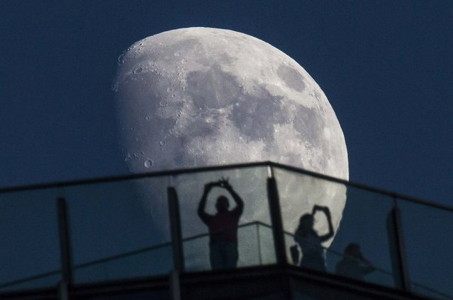 Visitors stand on the roof of a skyscraper as the moon rises over the skyline in Shanghai, on August 16, 2013. (Photo by Aly Song/Reuters)
