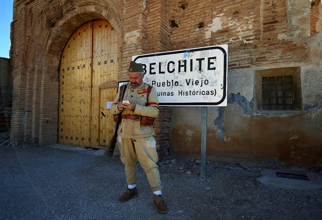 A man dressed up as a Republican soldier looks at his mobile phone as he waits for tourists in front of the entrance to the old village of Belchite, in northern Spain, November 14, 2016. (Photo by Andrea Comas/Reuters)
