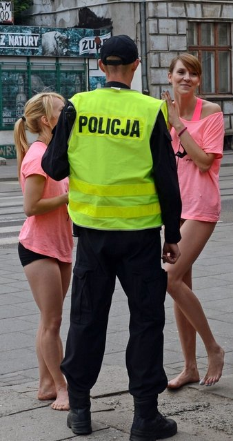 "A police officer talks to members of the ""Avocadoo"" club after they performed a pole dance on a street sign pole in Lodz, central Poland on June 27, 2013. Talk about a traffic stopper: three pole dancers in central Poland have been honing their skills out in the streets, throwing their legs around signposts to the surprise and delight of many a passerby. (Photo by Janek Skarzynski/AFP Photo)"