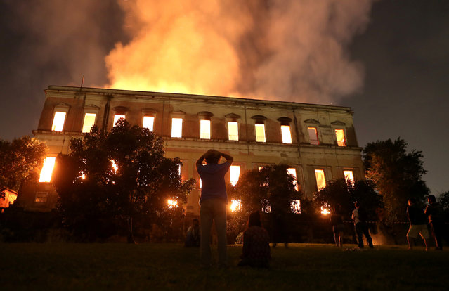 People watch as a fire burns at the National Museum of Brazil in Rio de Janeiro on September 3, 2018. The majestic edifice stood engulfed in flames as plumes of smoke shot into the night sky, while firefighters battled to control the blaze that erupted around 2230 GMT. Five hours later they had managed to smother much of the inferno that had torn through hundreds of rooms, but were still working to extinguish it completely, according to an AFP photographer at the scene. (Photo by Ricardo Moraes/Reuters)