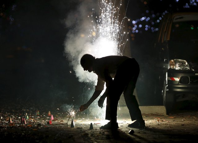 A man lights firecrackers on the street during the New Year celebrations in Mumbai, India, January 1, 2016. (Photo by Danish Siddiqui/Reuters)